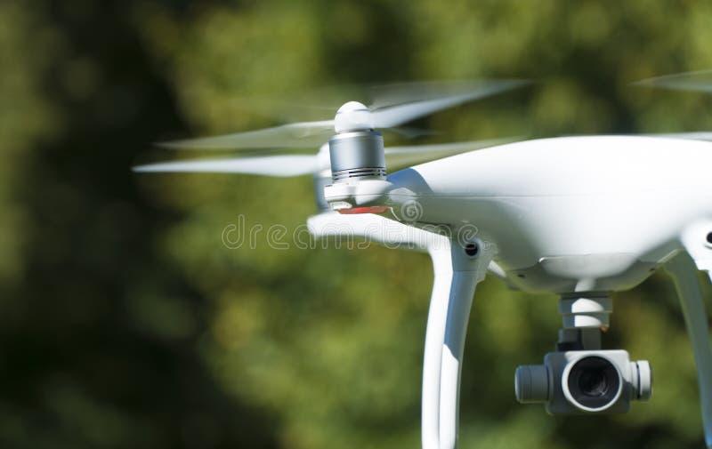 Hélicoptère blanc de quadruple de bourdon avec le parc d'été photos libres de droits