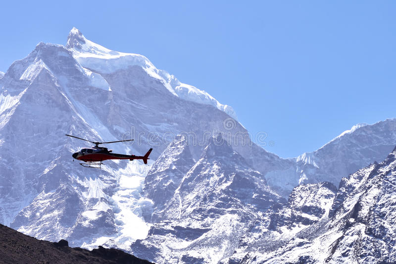 Hélicoptère de délivrance en vol au-dessus de la neige couverte images stock