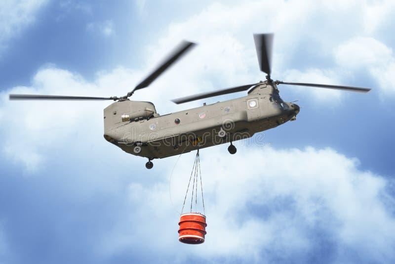 Hélicoptère de lutte contre l'incendie du vol italien d'armée avec un seau vide en métal pour s'éteindre un feu photos stock