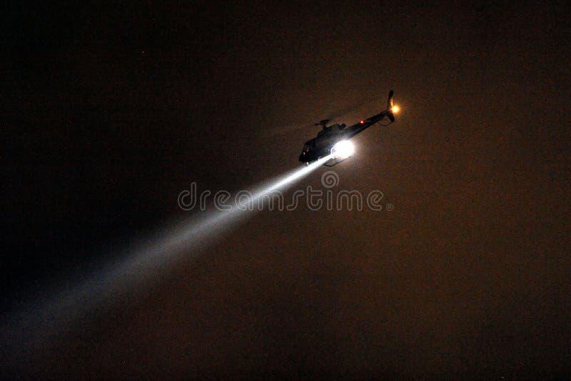 Hélicoptère de police avec le projecteur la nuit image stock