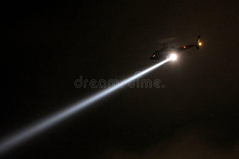 Hélicoptère de police avec le projecteur la nuit photographie stock libre de droits