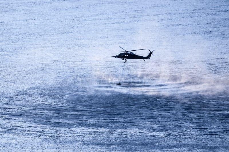 Hélicoptère militaire planant au-dessus de la rivière photo stock