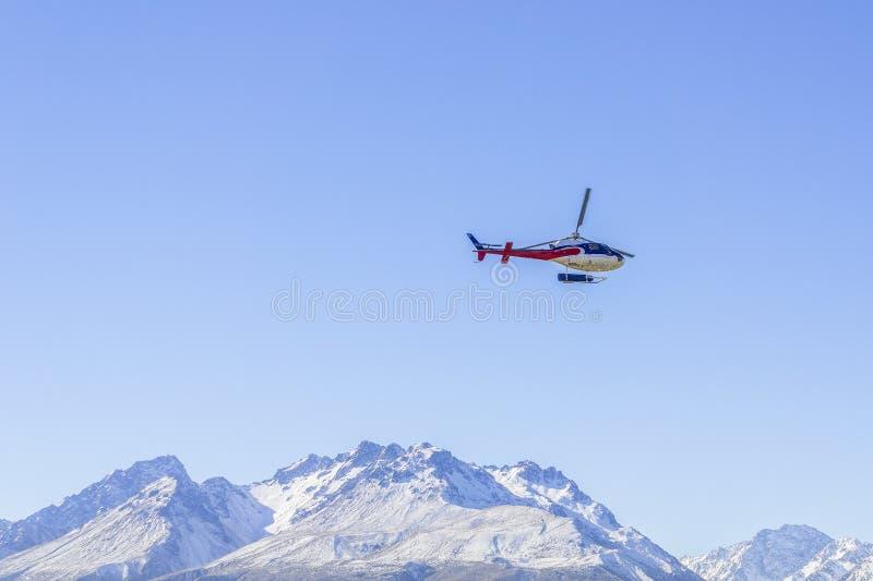 Hélicoptère non identifié volant au-dessus de la côte ouest étonnante, île du sud, Nouvelle-Zélande photo stock