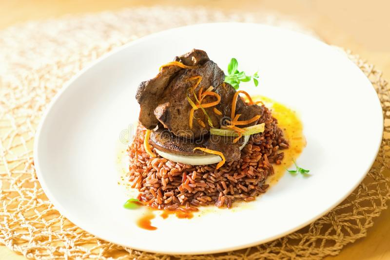 Hígado asado del cerdo, arroz moreno natural, verdura, porción en la placa blanca foto de archivo libre de regalías