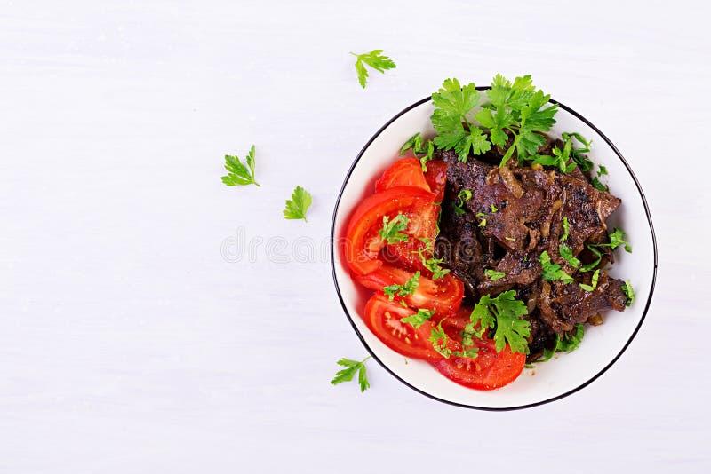 Hígado asado o asado a la parrilla de la carne de vaca con la cebolla y la ensalada de los tomates fotografía de archivo