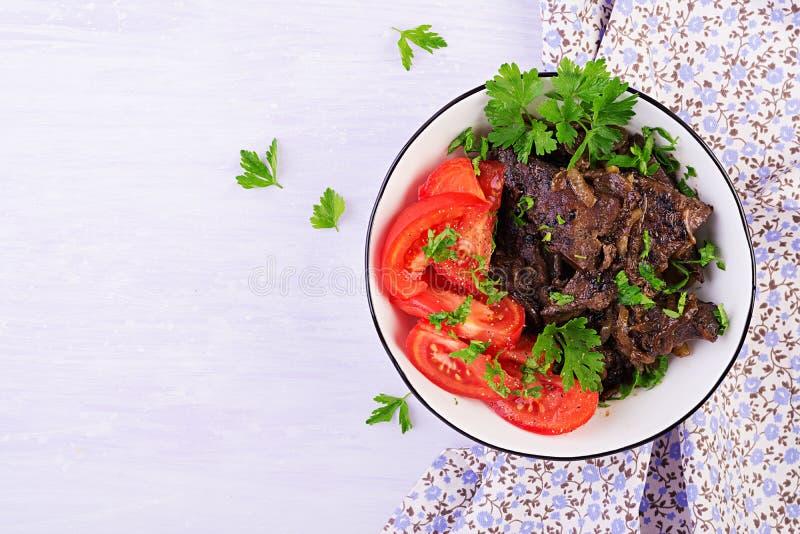 Hígado asado o asado a la parrilla de la carne de vaca con la cebolla y la ensalada de los tomates imagen de archivo
