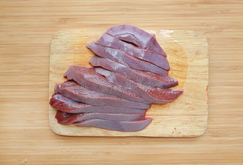 Hígado cortado fresco crudo del cerdo en fondo del tablero de madera imágenes de archivo libres de regalías