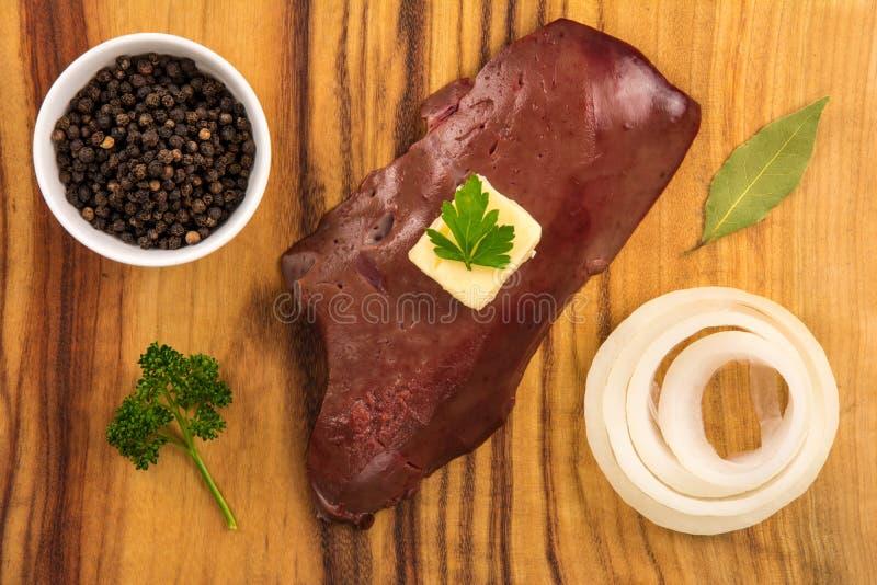 Hígado crudo de la ternera en el tablero de madera con mantequilla, la cebolla, la pimienta negra, el laurel y el perejil fotografía de archivo