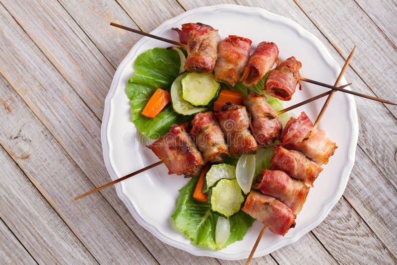 Hígado de pollo envuelto con tocino en los pinchos Kebabs asados a la parrilla del hígado con las verduras imagenes de archivo