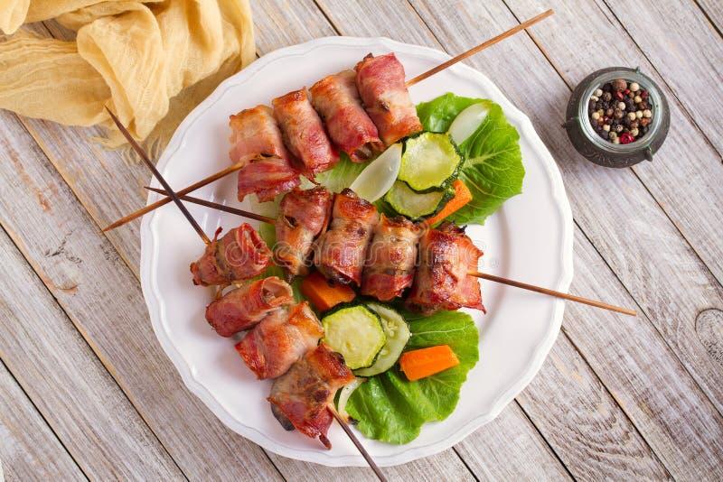Hígado de pollo envuelto con tocino en los pinchos Kebabs asados a la parrilla del hígado con las verduras fotografía de archivo