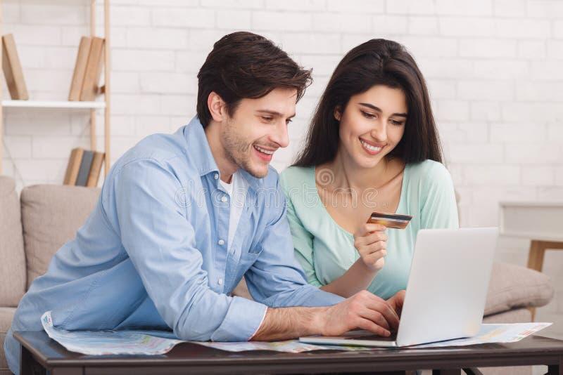 Hôtel de réservation de couples heureux en ligne sur l'ordinateur portable image stock