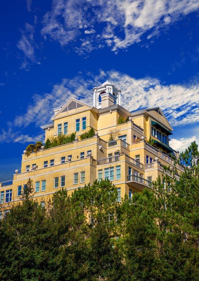 Hôtel jaune de stuc se levant hors des arbres dans le ciel bleu photos stock
