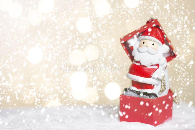 Hôtes et arbre miniatures de Santa de Noël sur la neige au-dessus du fond brouillé de bokeh, de l'image de décoration pour des va image stock
