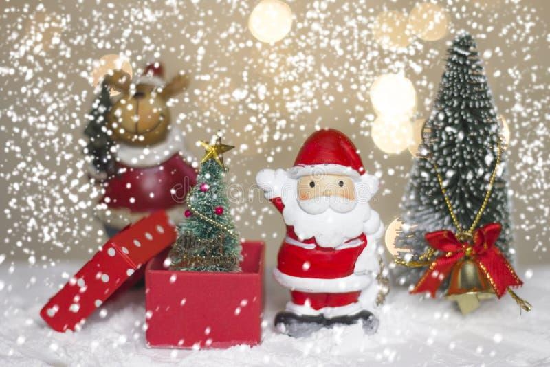Hôtes et arbre miniatures de Santa de Noël sur la neige au-dessus du fond brouillé de bokeh, de l'image de décoration pour des va photos stock