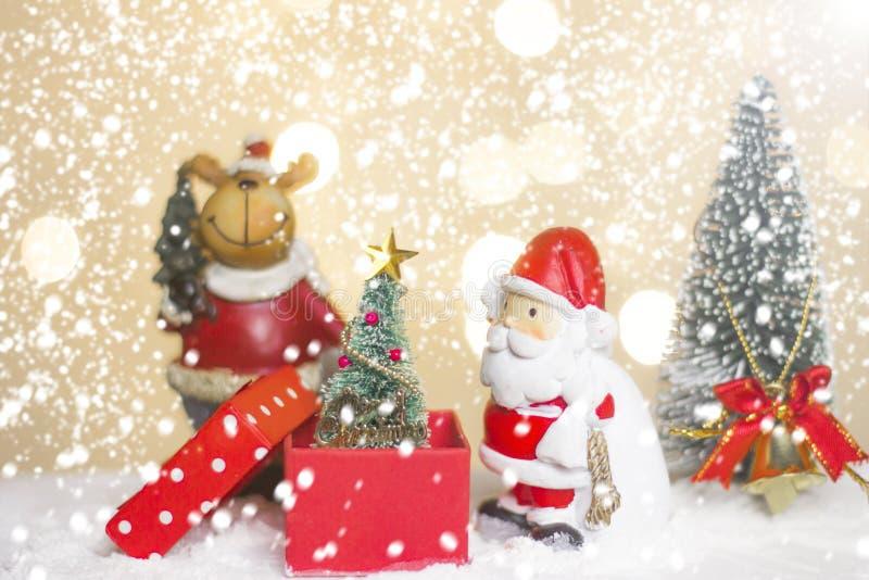 Hôtes et arbre miniatures de Santa de Noël sur la neige au-dessus du fond brouillé de bokeh, de l'image de décoration pour des va image libre de droits
