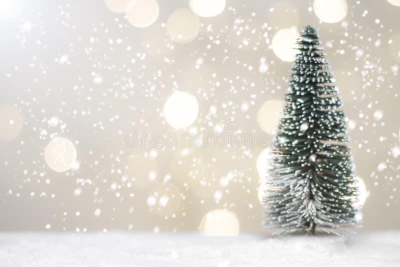 Hôtes et arbre miniatures de Santa de Noël sur la neige au-dessus du fond brouillé de bokeh, de l'image de décoration pour des va images stock
