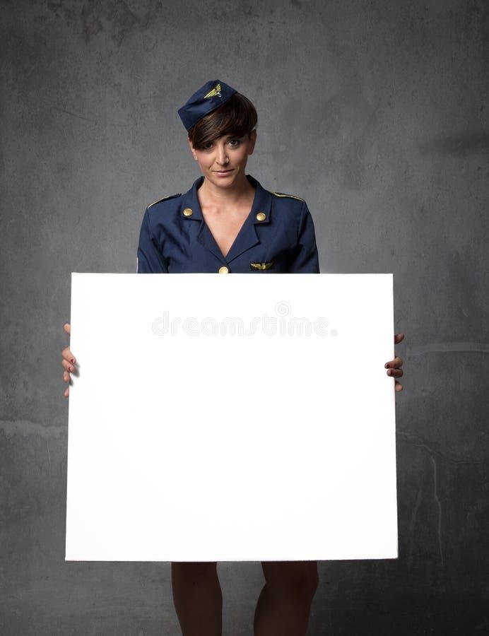 Hôtesse de l'air avec le conseil vide blanc en main photo stock