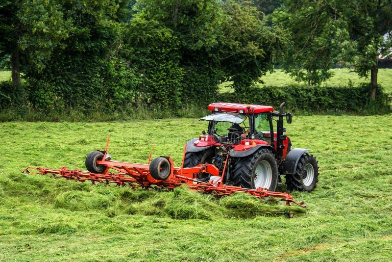 Hödanande med traktor- och hötedderen royaltyfria foton