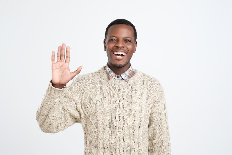 Höflicher junger Afroamerikanermann gekleidet in der sagenden Strickjacke hallo lizenzfreie stockfotos