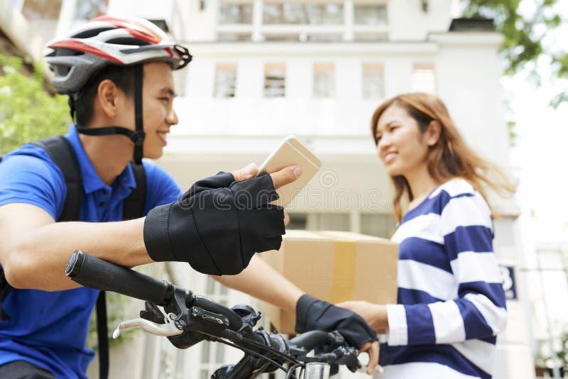 Höfling mit dem Smartphone, der weiblichen Kunden betrachtet stockfotos
