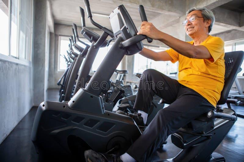 Hög äldre man som övar på att cykla maskinen som kopplar av i konditionidrottshall igen Gammal manlig genomkörare Mogen sportutbi arkivfoton