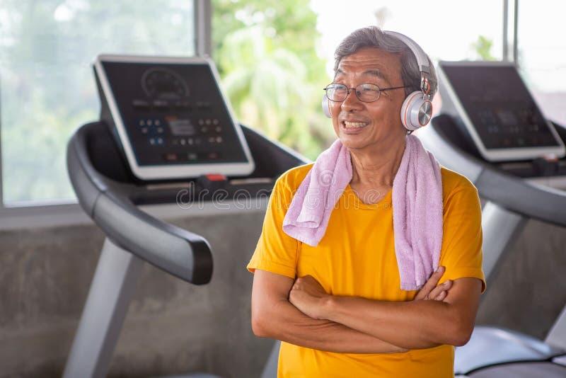 Hög äldre man som tar ett avbrott från lyssnande musik för genomkörare med hörlurar som kopplar av i konditionidrottshall igen ga royaltyfri foto
