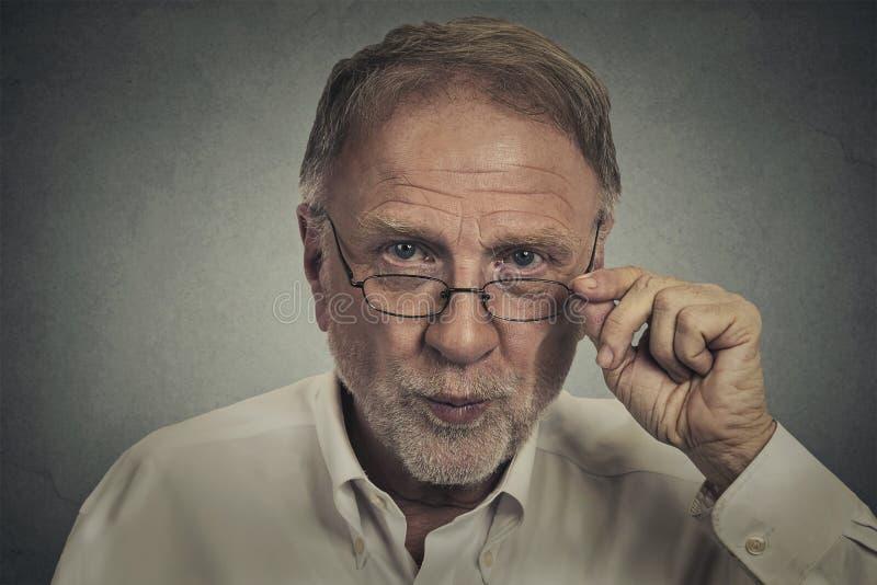 Hög äldre skeptisk man med glasögon royaltyfri fotografi
