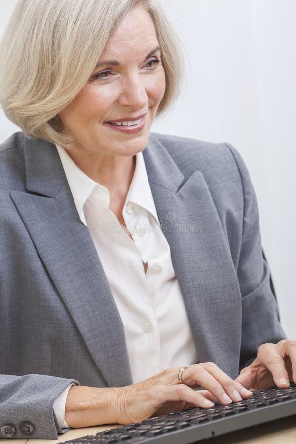 Hög affärskvinna genom att använda datoren royaltyfri foto