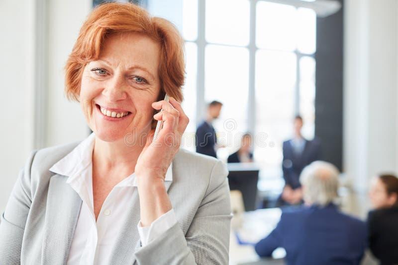 Hög affärskvinna med smartphonen arkivfoto