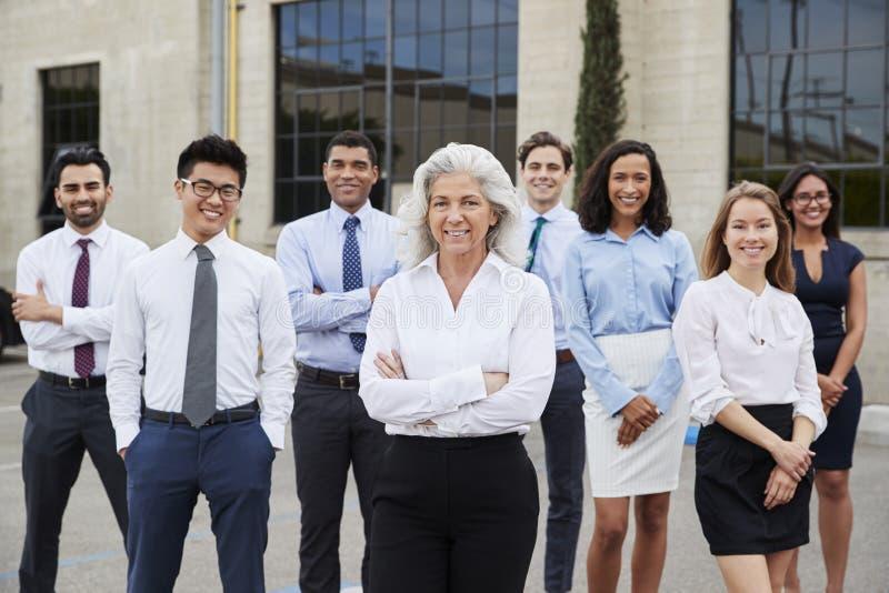 Hög affärskvinna och kollegor utomhus, stående arkivbilder