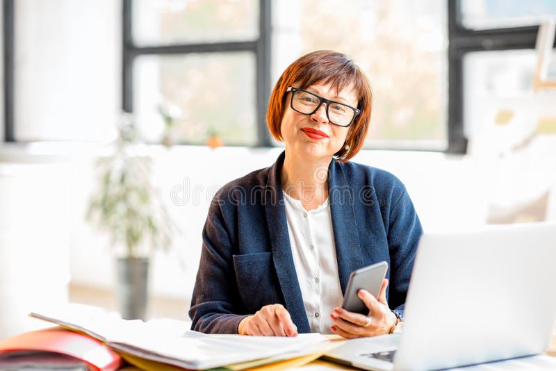 Hög affärskvinna på kontoret arkivbild