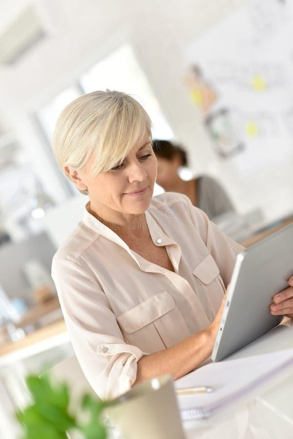 Hög affärskvinna på kontoret genom att använda minnestavlan royaltyfria bilder