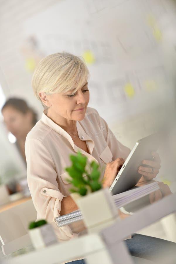 Hög affärskvinna som använder minnestavlan på kontoret arkivfoto
