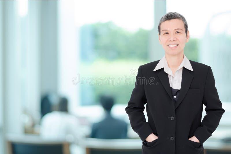 Hög affärskvinna som arbetar på kontoret royaltyfri foto