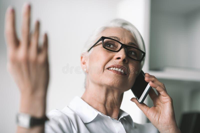 Hög affärskvinna som talar på telefonen royaltyfria foton