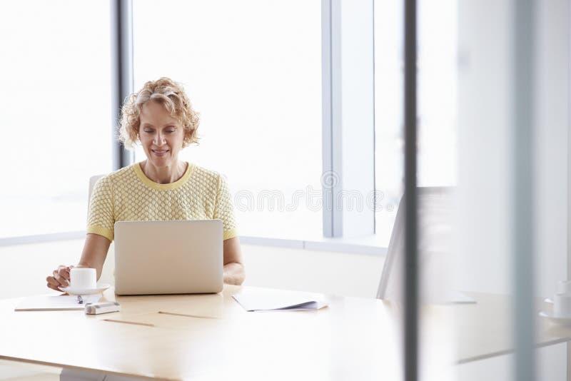 Hög affärskvinna Working On Laptop på styrelsetabellen arkivbild