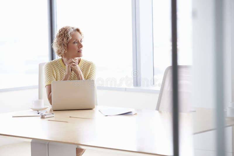 Hög affärskvinna Working On Laptop på styrelsetabellen royaltyfri bild