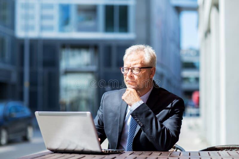 Hög affärsman med bärbara datorn på stadsgatakafét arkivbilder