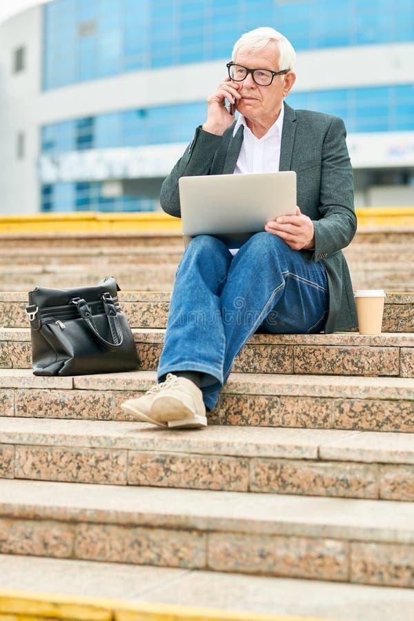 Hög affärsman med bärbara datorn som talar på smartphonen arkivbilder