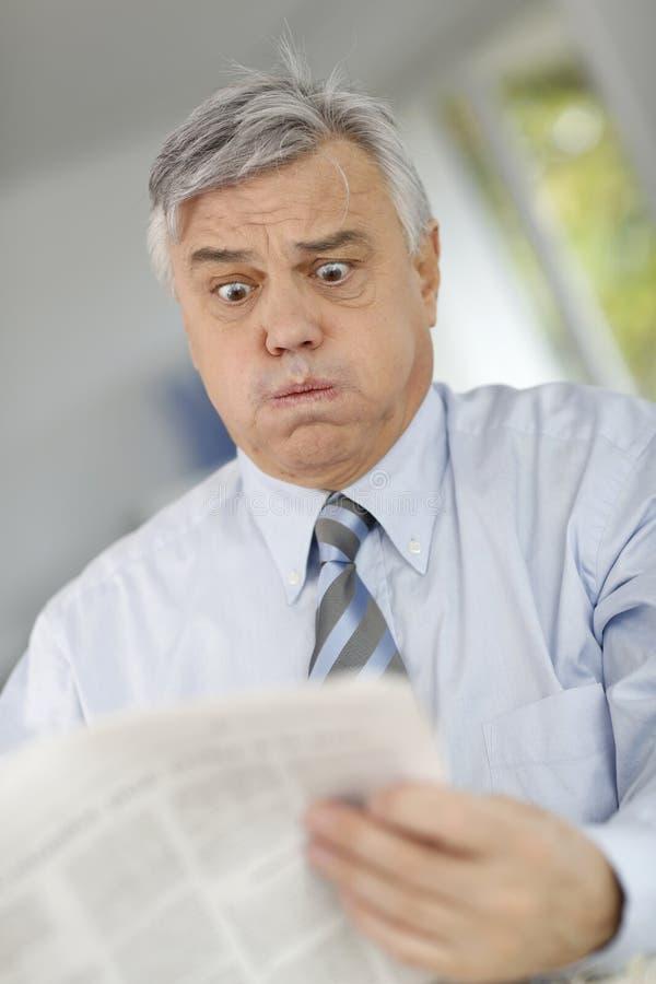 Hög affärsman med förfärat med nyheterna royaltyfria foton