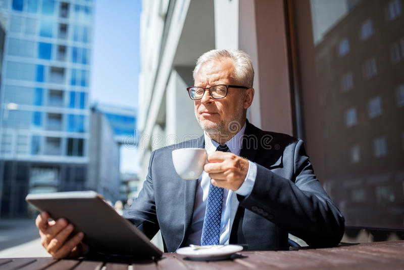 Hög affärsman med minnestavlaPC som dricker kaffe royaltyfria bilder