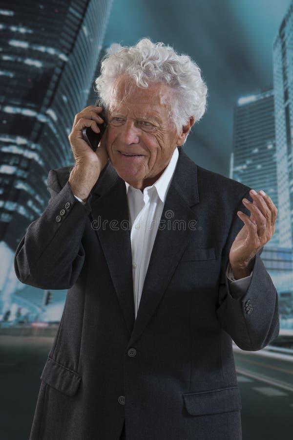 Hög affärsman med mobiltelefonen royaltyfri foto