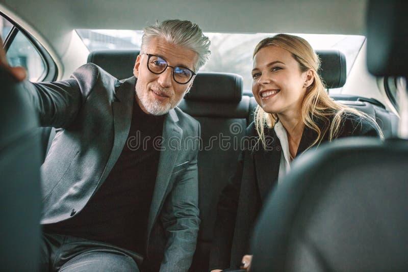 Hög affärsman och hans assistentresande med taxien arkivfoto