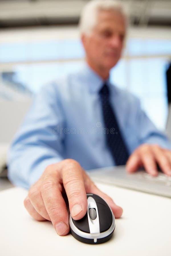 Hög affärsman på bärbar dator royaltyfri foto