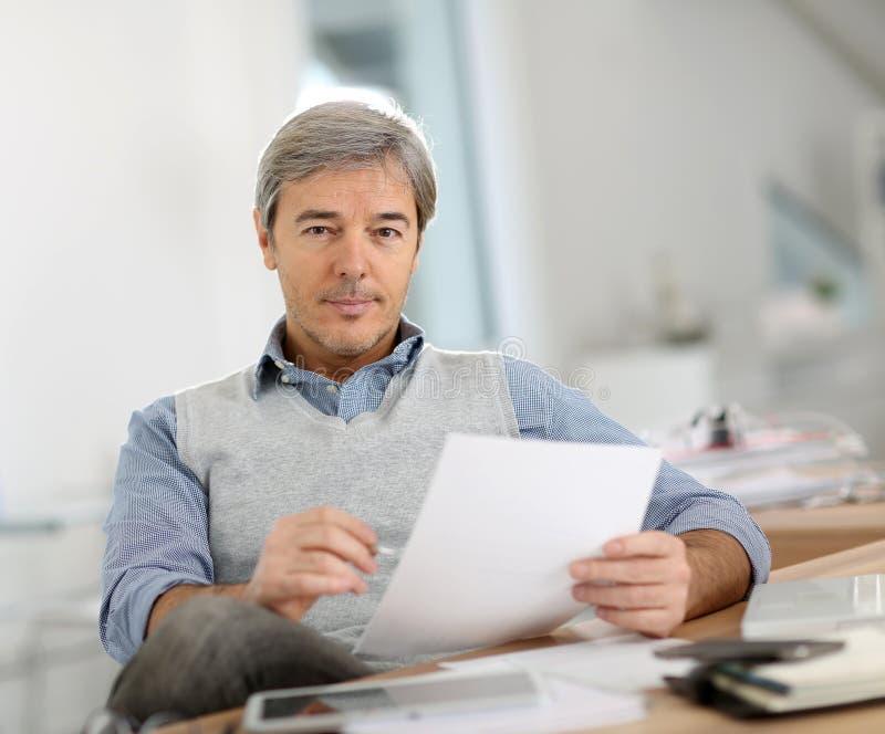 Hög affärsman på kontoret arkivfoton