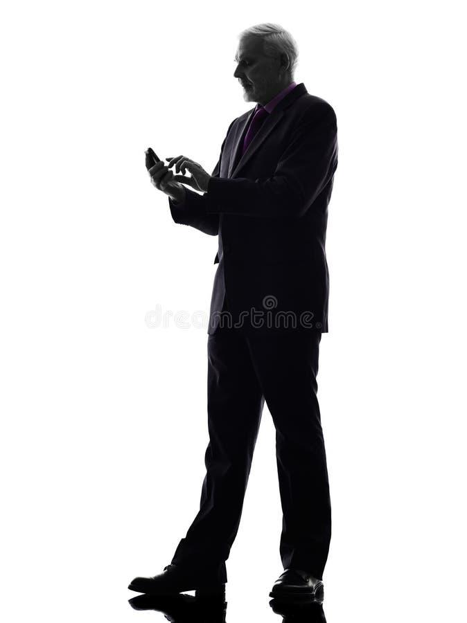 Hög affärsman på konturn för telefontextmessaging arkivbilder