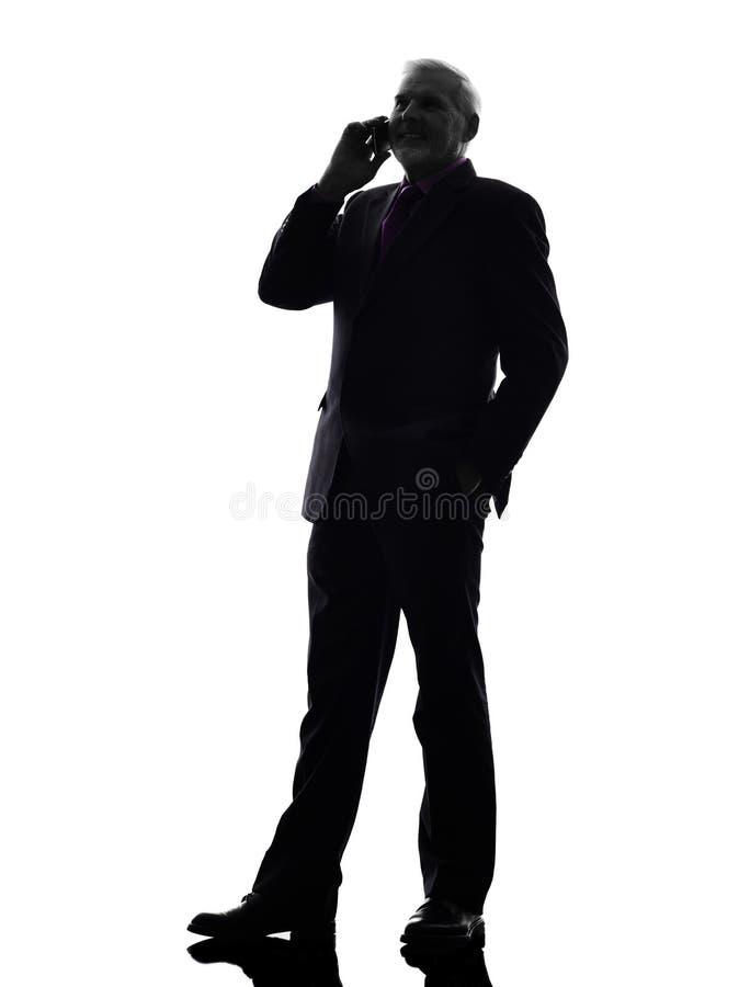 Hög affärsman på telefonen som ler konturn royaltyfria foton