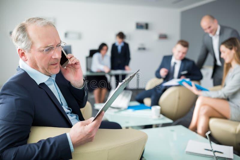 Hög affärsman Reading Document While som in använder Smartphone av arkivbild