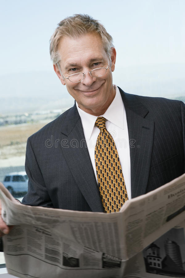 Hög affärsman Reading Newspaper arkivfoton