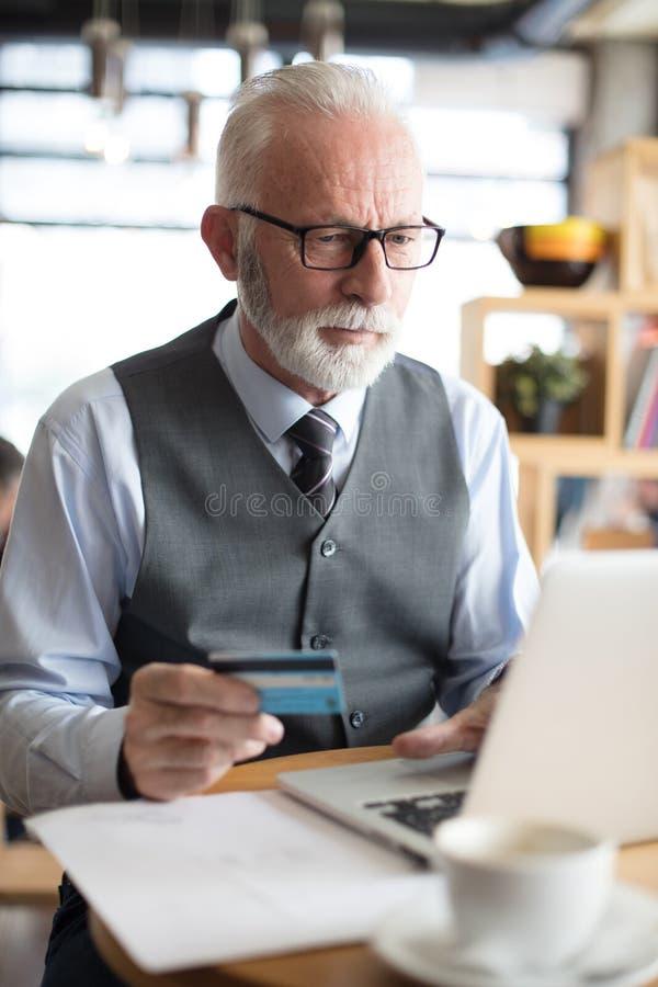 Hög affärsman som använder bärbara datorn för att kontrollera kreditkorten royaltyfri fotografi